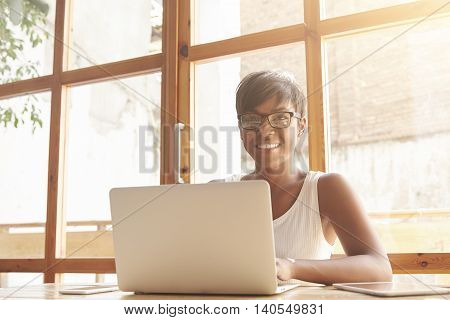 Adult Self-confident Smiling Dark-skinned Female Web Manager Dressed Casually Looking At The Camera