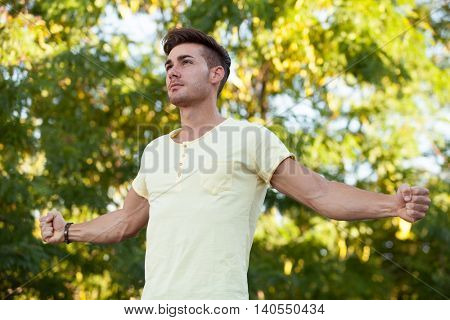Attractive guy in the park with yellow t-shirt extending his strong arms
