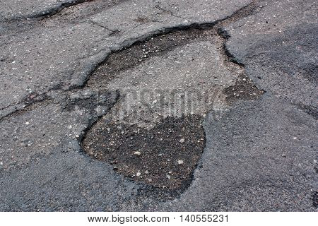 Dangerous road with holes destroyed asphalt way