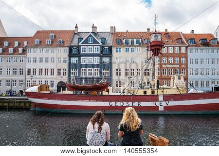 Copenhagen Denmark - July 20 2015: Two ladies sitting on the bank of the Nythavn canal with raditional houses and boats in the background