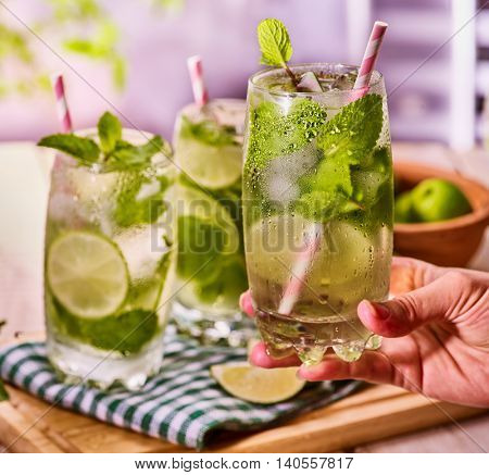 On wooden boards three glasses with alcohol drink and ice cubes. Drink three hundred and eleven cocktail mohito with female hand and lime and mint leaf. Country life. Outdoor. Light background.