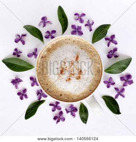 flat lay frothy coffee with cinnamon garnished with flowers of lilac top view / Cappuccino with aroma cinnamon and lilac