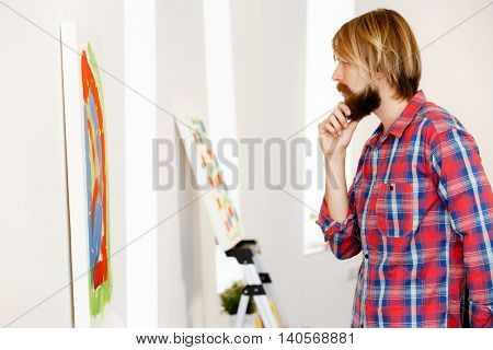 Man standing in a gallery and contemplating artwork