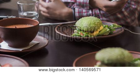 Vegan hamburger and cherry tomatoes are nice idea for vegan person. Vegan restaurant or cafe. Picture of vegan dish represented on plate.