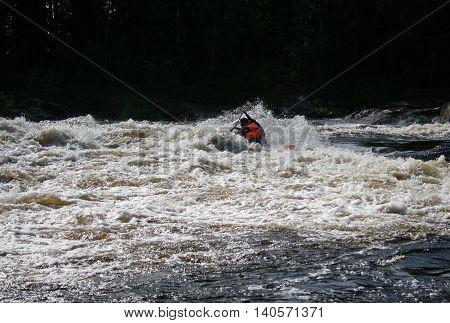 KOLA PENINSULA RUSSIA - 17 AUGUST 2008: Team of men on an inflatable catamaran at rough river.