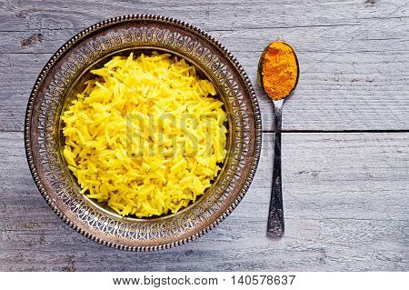 Top view of an antique metal bowl with cooked turmeric jasmine rice and vintage metal teaspoon with powdered curcumin