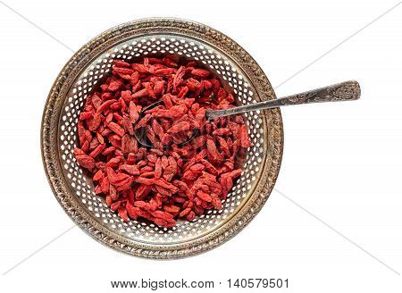 Antique metal bowl of raw dried goji berries with vintage teaspooned inside isolated on white