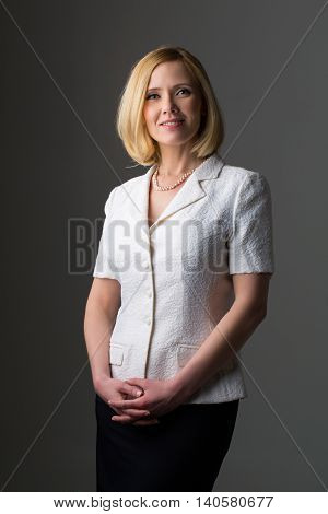 Portrait of elderly business woman in feminine suit. Happy smiling expression. Over grey background. Copy space.