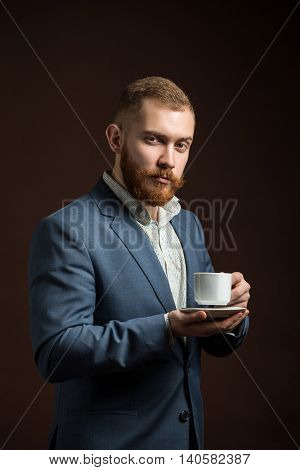 Portrait of red haired elegant man in suit with cup of coffee looking at camera.Isolated.