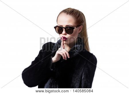 Portrait of attractive blonde model in fur coat with finger over lips looking at camera.Isolate