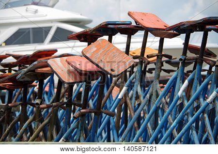 Dry dock boat jacks piled with sailing marina background