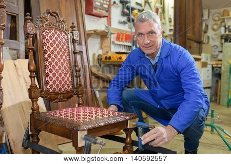 older man restoring a chair