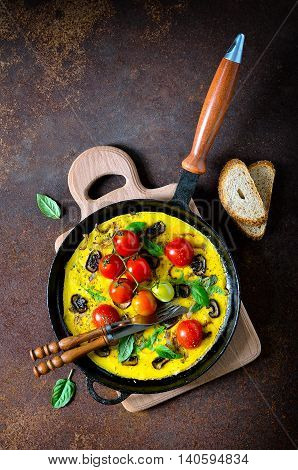 Frittata or omelet with mushrooms and tomatoes in a pan traditional mediterranian course top view vertical