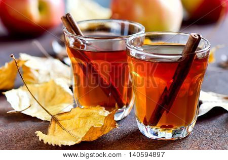Apple cider with cinnamon sticks in glasses decorated with autumn yellow leaves