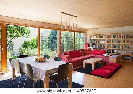 Living room of an eco house, dining table and red divan