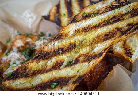 Fresh hot garlic toast with grill marks in basket