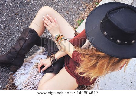Fashion woman dressed in boho chic style sitting on a street, cowboy boots, hat on a head, many bracelets on a hands, top view, no face