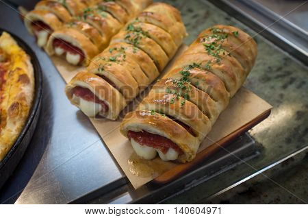 Fresh hot pepperoni and cheese Italian stromboli on display