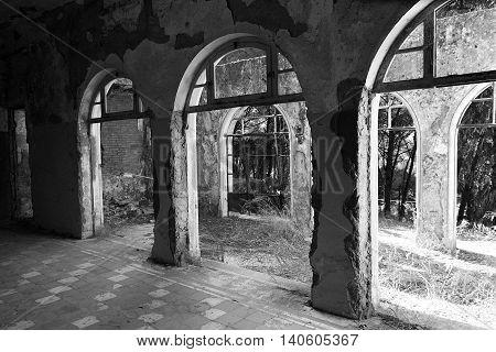 Old abandoned sanatorium and view through arcs