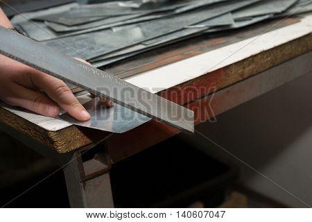Artisan polishes sharp metal edge - closeup trade