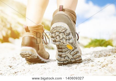 Woman hiker walk on a rocky ground. Sunny day.Trekking boots.Lens flare. Succesful backpacker. Stone. Step