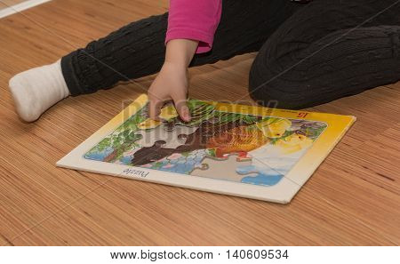 Child playing with a big puzzle - closeup