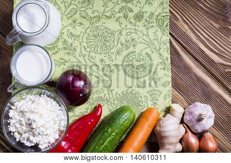Frame of fresh vegetables and dairy products on wooden background. The concept of proper nutrition and a healthy lifestyle. Food for dairy-vegetable diet with copy space flat lay.