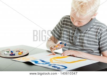Creative Young Boy Finger Painting At Home