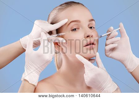 Portrait of young blonde woman taking care of her face skin with botox syringes