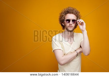 Portrait of curly-haired young man in sunglasses looking confused at camera.Isolate.Yellow background.