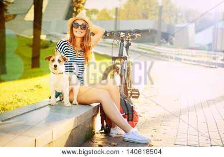 Smiling Hipster Girl with her Dog and Bike in City. Happy Woman Enjoying Summer Lifestyle with Pet. Toned and Filtered Photo.