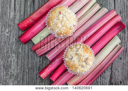 Top View on two Rhubarb muffins in paper cups on a rhubarb perioles on Old Wooden Board
