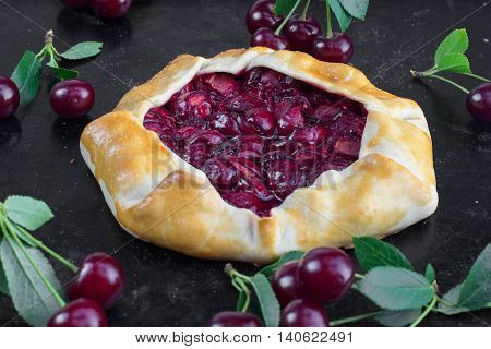 Delicious Rustical Sour Cherry Pie on Black Background with a few sour cherries