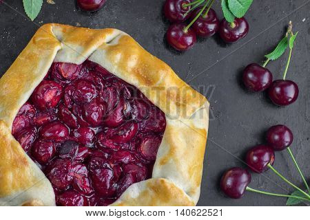 Top View on Delicious Rustical Sour Cherry Pie on Black Background with a few sour cherries