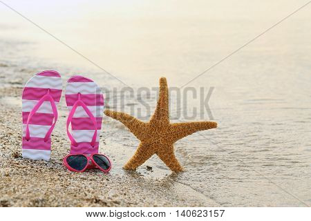 Pink Sunglasses With Pair Of Flip Flops And Starfish On The Beach Sand