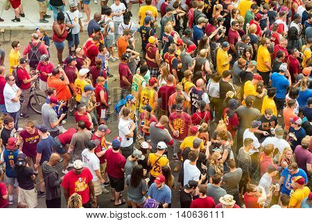 CLEVELAND OH - JUNE 22 2016: Cavs fans mingle in the streets wearing team colors and apparel in anticipation of the Cleveland Cavaliers' NBA championship parade.