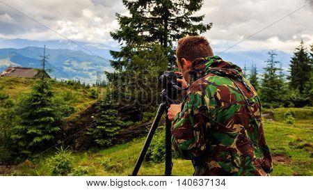 Photographer taking photo on tripod of mountain landscape in Carpathian Ukraine