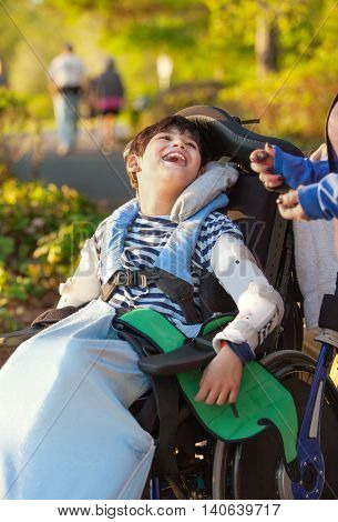 Smiling nine year old boy in wheelchair enjoying time at park outdoors