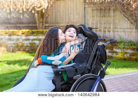 Sister kissing and hugging disabled little nine year old brother in wheelchair outdoors
