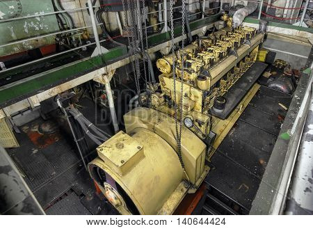 Yellow engine mounted on ship. Engine room on a old cargo boat ship.