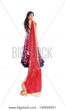 A lovely woman standing in a blue dress and long black hair holding a long red vail isolated for white background.