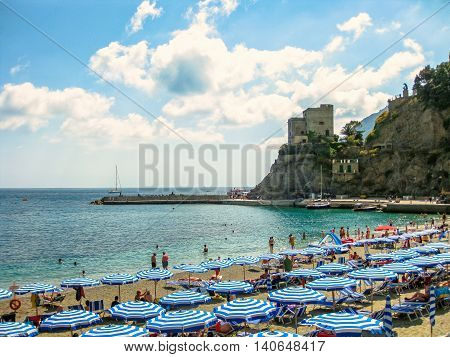 Monterosso al Mare, Ligurian Coast, Italy - June 4, 2010: beach umbrellas, deck chairs and people sunbathing in popular Monterosso Beach, the largest village of the Cinque Terre National Park.