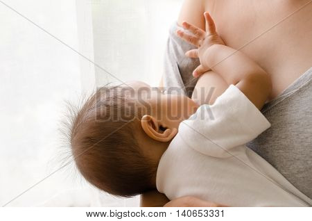 Mother breastfeeding her newborn baby beside window poster
