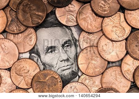 A five dollars banknote with a lot of pennies around it