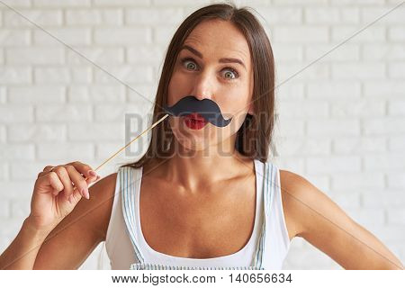 Amazing pretty woman wear white singlet and holding mustache-mask, white brick wall on background