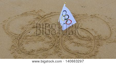 Sydney, Australia - Jul 31, 2016. Olympic rings drawn in the sand and olympic flag in the centre. Summer Olympic Games