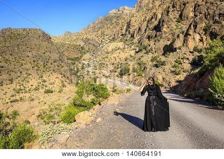 A woman in black abaya is walking on a road in Al Hajar Mountains in Oman