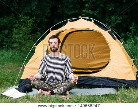 Young man practicing yoga in meditation pose, camping background. Healthy lifestyle, deep unity with nature, nirvana