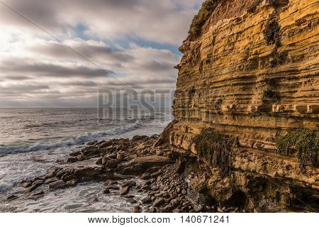 Side of cliff with rocks and ocean at Sunset Cliffs in San Diego, California.