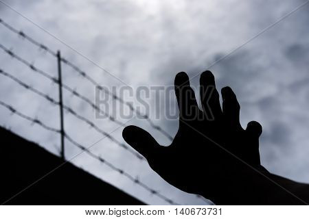 Silhouette hand extending to the sky with defocus barbwire, on gloomy overcast sky poster